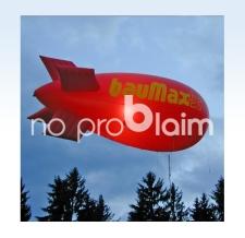 fliegender Werbezeppelin mit Werbung - Baumax